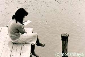 昭和の桟橋で本を読む少女